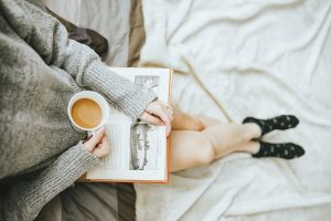 Girl reading a book with a cup of coffee. She has a green top, and pale skin. This photo is shot from the sky looking down, you cann see her torso and legs. She's sitting on her bed.