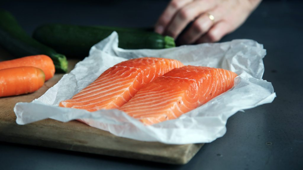 Photo of 2 salmon fillets on foil, with a mans hand in the background getting ready to cook them.