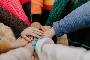 many people with brightly colored sweaters, with their arms in the center to begin a teamwork cheer.