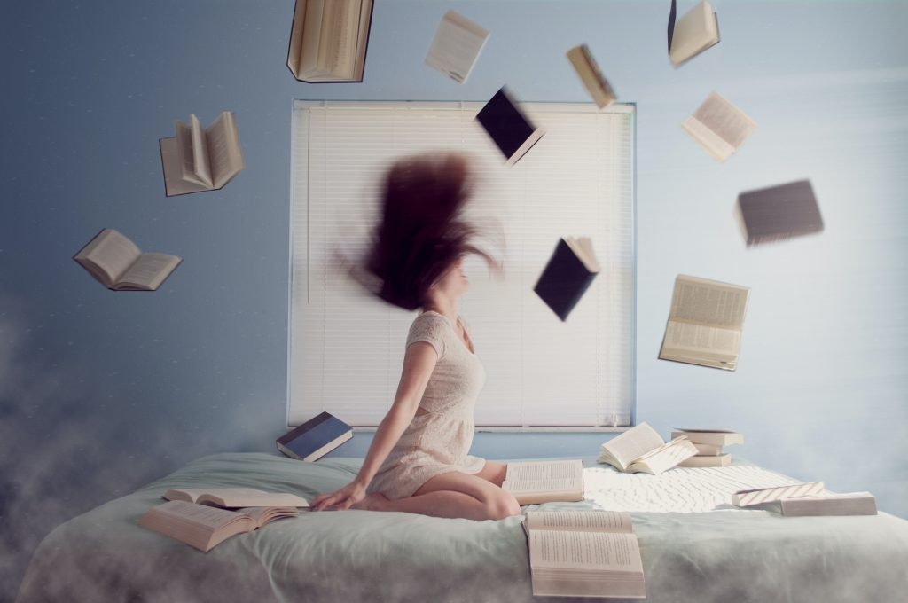 Photo of blurry, brunette woman, with books flying around her in the air.